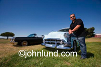 Stock photo of a hispanic man leaning on his classic vintage car with his foot on the bumper and his hand on his knee. Blue jeans, black shirt , sunglasses, blue sky, green grass, Northern California.